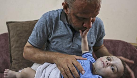 Mohammad al-Hadidi en la casa de su hermano sosteniendo a su hijo Omar, quien fue sacado con vida de debajo de los escombros mientras su madre y cuatro hermanos murieron en un ataque aéreo israelí en Gaza. (Foto de MAHMUD HAMS / AFP).