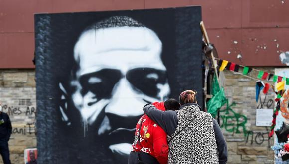 Una pareja se detiene por un momento frente a un retrato de George Floyd en Minneapolis en el segundo día de deliberaciones para la sentencia al policía Derek Chauvin. (EFE / EPA / CRAIG LASSIG).