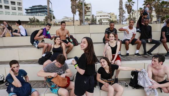 Los jóvenes se reúnen en la ciudad costera israelí de Tel Aviv el 19 de abril de 2021, después de que las autoridades anunciaran que ya no se necesitaban mascarillas faciales como protección contra el coronavirus. (Foto por menahem kahana / AFP).