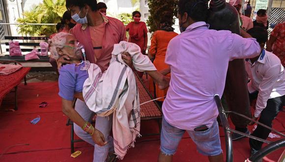 Un miembro de la familia lleva a un paciente que respira con la ayuda del oxígeno que le proporciona un Gurdwara, un lugar de culto para los sijs, debajo de una carpa instalada a lo largo de la carretera en Ghaziabad, el 4 de mayo de 2021. (Tauseef MUSTAFA / AFP).