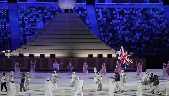 Hannah Mills y Mohamed Sbihi, de Gran Bretaña, portan la bandera de su país durante la ceremonia de inauguración de los Juegos Olímpicos de Tokio 2020 en el estadio olímpico el 23 de julio de 2021 en Tokio, Japón. (Foto AP/Kirsty Wigglesworth)