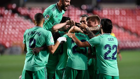 Real Madrid's players celebrate after French defender Ferland Mendy scored during the Spanish league football match Granada FC vs Real Madrid CF at Nuevo Los Carmenes stadium in Granada on July 13, 2020. / AFP / JORGE GUERRERO