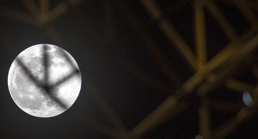 Una fotografía tomada el 10 de enero de 2020 muestra la luna llena saliendo detrás de las decoraciones navideñas de la calle durante el eclipse lunar penumbral en Skopje (Foto: AFP)