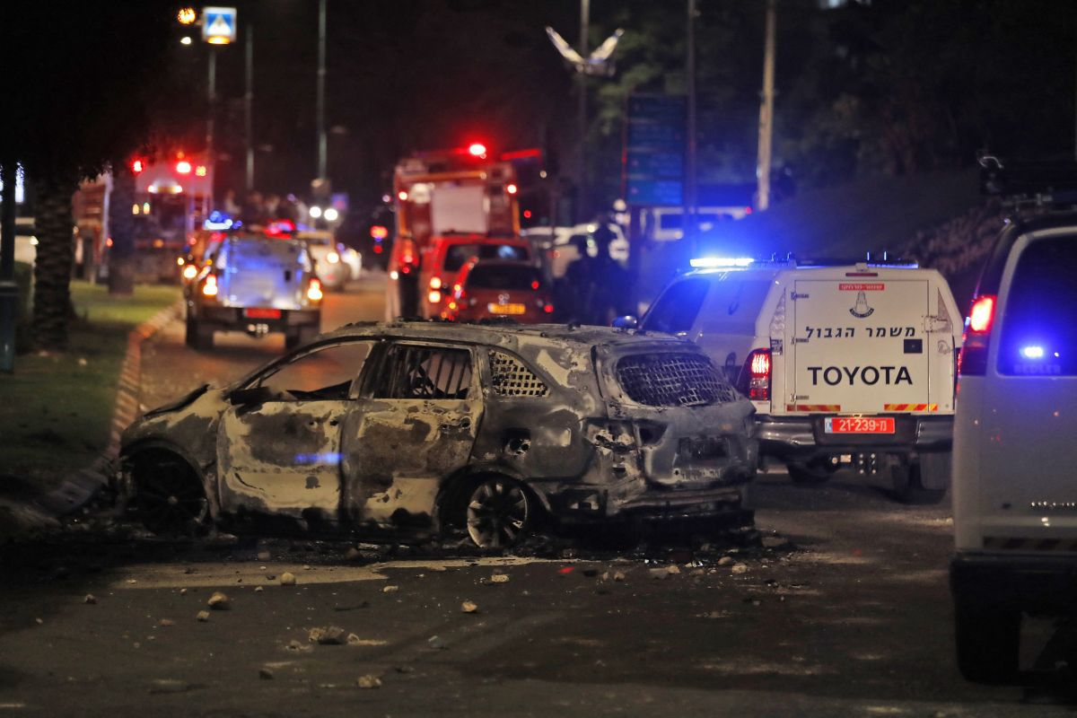 Israeli border police vehicles pass a burned-out car in Lod, near Tel Aviv, on May 11, 2021. (Photo: AFP).