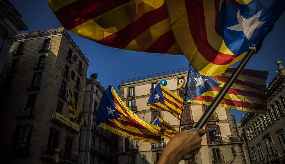 """People wave independence flags just after the speech of Catalan regional president Carles Puigdemont in Barcelona, Spain, Thursday, Oct. 26, 2017. Puigdemont said Thursday he considered calling a snap election, but was choosing not to because he didn't receive enough guarantees that the government's """"abusive"""" moves to take control of Catalonia would be suspended. (AP Photo/Santi Palacios)"""