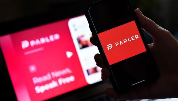 En esta foto de archivo tomada el 1 de julio de 2020 se ve una imagen del logotipo de la aplicación de redes sociales de Parler en un teléfono inteligente con su sitio web de fondo. (Foto de Olivier DOULIERY / AFP).