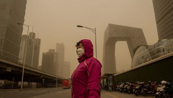 Una mujer espera en una parada de autobús durante una tormenta de arena en el distrito financiero de Beijing el 15 de marzo de 2021. (Foto de NICOLAS ASFOURI / AFP).