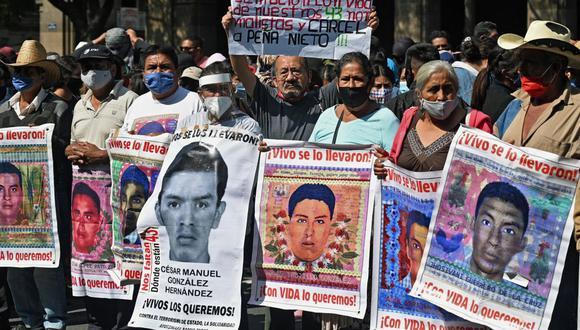 Familiares de los 43 estudiantes desaparecidos de la Escuela Rural de Maestros de Ayotzinapa sostienen retratos de ellos durante una protesta frente a la sede de la Corte Suprema en la Ciudad de México, el 23 de septiembre de 2020. (Foto de ALFREDO ESTRELLA / AFP).
