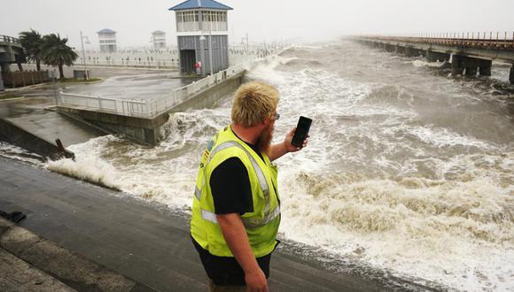 Un trabajador de servicios públicos fotografía las olas cuando chocan contra un malecón mientras las bandas exteriores del huracán Ida llegan a Bay Saint Louis, Mississippi. (Foto AP / Steve Helber).