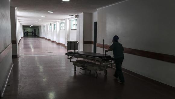 Un trabajador de la salud mueve una camilla por un pasillo del Hospital Universitario, uno de los más importantes en la formación de médicos en Venezuela. (Foto de Pedro MATTEY / AFP).