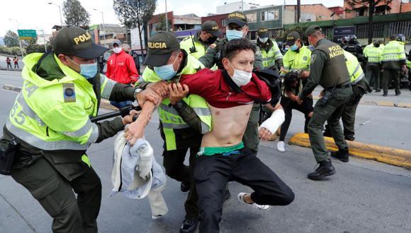 Integrantes de la Policía de Colombia detienen a un hombre en una vía bloqueada por comerciantes como protesta por un nuevo confinamiento en el sector de Venecia en Bogotá (Colombia). (Foto: EFE/Mauricio Dueñas Castañeda).