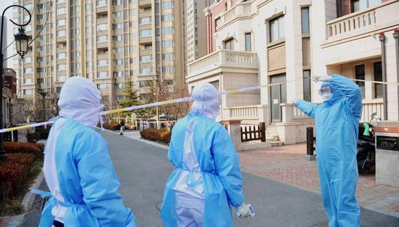 Varios trabajadores visitan a una familia en cuarentena por coronavirus en Qingdao, provincia de Shandong, China. (EFE/EPA/YU FANGPING/Archivo).