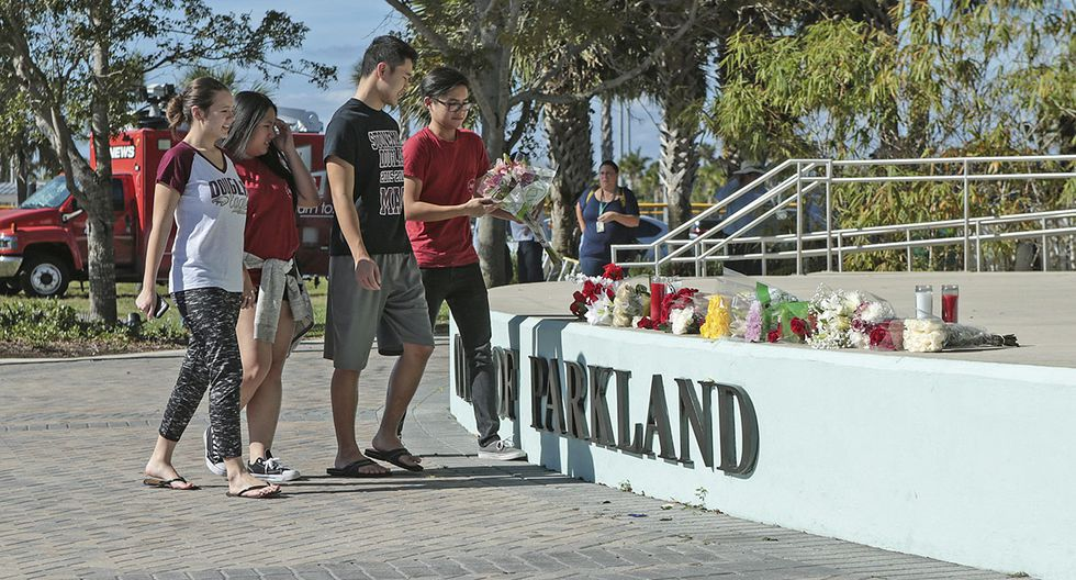 Students place flowers on the stage outside the Pines Trail Center where a candlelight vigil will be held, Thursday, Feb. 15, 2018, in Parkland, Fla. Nikolas Cruz is accused of opening fire Wednesday at Marjory Stoneman Douglas High School in Parkland, Fla., killing more than a dozen people and injuring several. (AP Photo/Joel Auerbach)