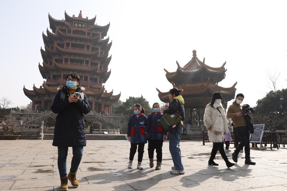 Personas con mascarillas visitan la Torre de la Grulla Amarilla en Wuhan, China. Para frenar la propagación de la enfermedad COVID-19, el gobierno chino cerró la ciudad de Wuhan durante 76 días a partir del 23 de enero de 2020 (Foto de Lintao Zhang / Getty Images).