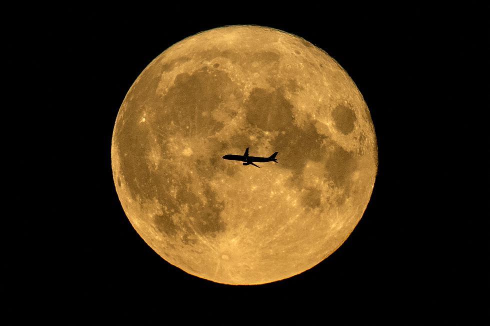 La silueta de un avión contra la luna llena en Moscú, el 22 de agosto de 2021. (Foto: Kirill KUDRYAVTSEV / AFP)