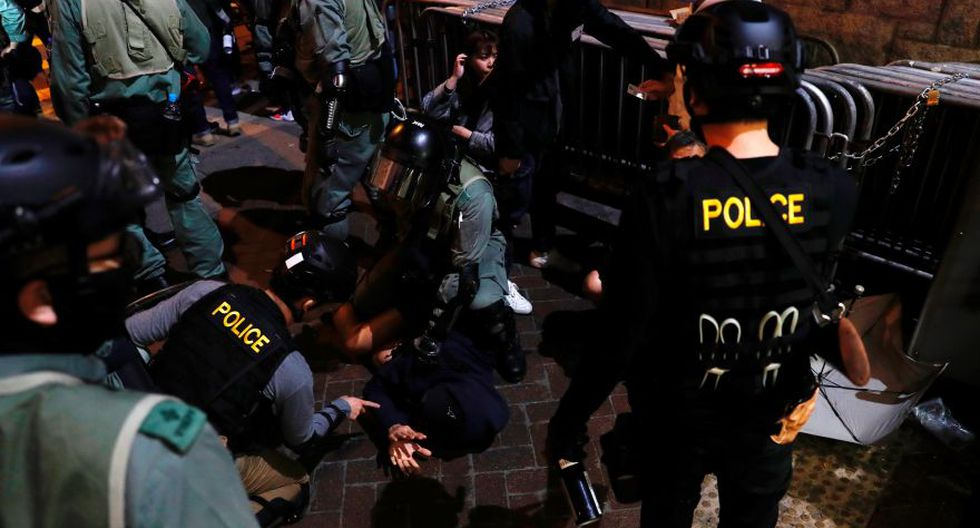 Agentes de la policía antidisturbios detienen a un manifestante antigubernamental durante una manifestación en Nochevieja frente a la estación de policía de Mong Kok. (Foto: Reuters).