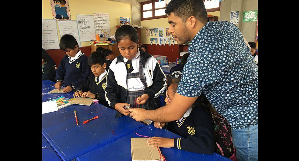 Alfredo Ruiz ayudando a las niñas del sexto grado con sus libros. (Foto: El Comercio)