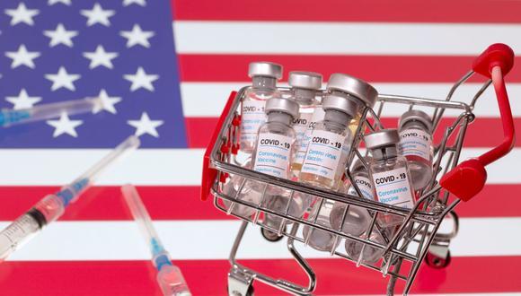"""Una pequeña canasta de compras llena de viales con la etiqueta """"COVID-19 y jeringas médicas se coloca sobre una bandera de Estados Unidos. (REUTERS / Dado Ruvic / Ilustración)."""