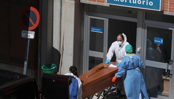 Trabajadores funerarios que usan trajes protectores sacan un ataúd de la morgue en el Hospital Severo Ochoa en Leganés, España, uno de los países más golpeados por el coronavirus. (REUTERS / Susana Vera).