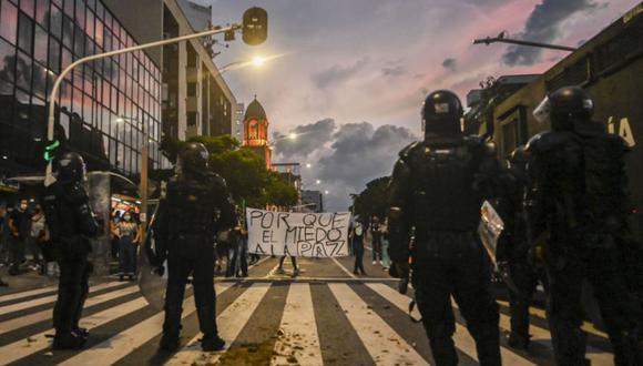 """Los manifestantes sostienen un cartel que dice """"¿Por qué el miedo a la paz?"""" frente a la policía antidisturbios durante una protesta contra la brutalidad policial en Medellín, Colombia, el 10 de septiembre del 2020. (Foto: JOAQUIN SARMIENTO / AFP)."""