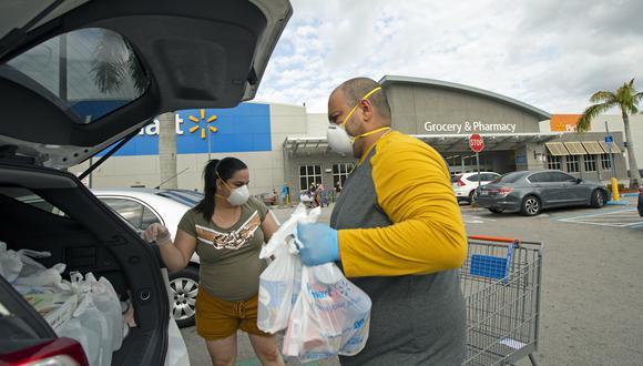 Coronavirus Estados Unidos   Miami   Una pareja de esposos coloca sus bolsas luego de realizar compras en un supermercado de Miami. Foto: David Santiago/Miami Herald via AP