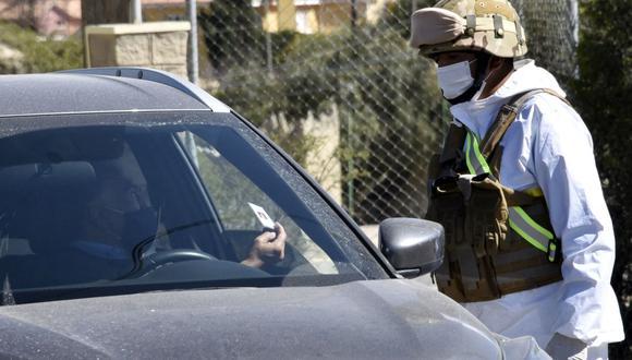 Imagen referencial. Un soldado con traje de protección detiene un automóvil en un puesto de control en Bolivia, el 20 de mayo de 2020. (AIZAR RALDES / AFP).