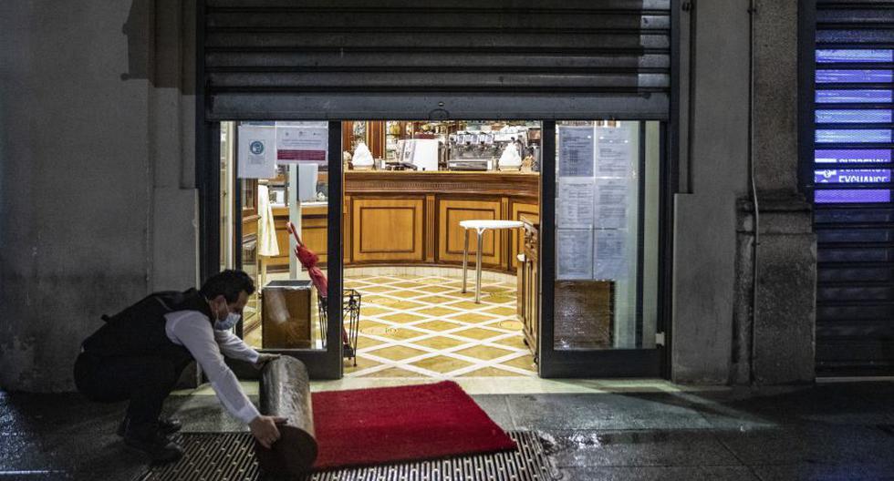 Esta imagen del último lunes muestra a un trabajador cerrando un café antes del toque de queda vigente en Milán, Italia. El país europeo impuso recientemente sus más fuertes restricciones contra el coronavirus COVID-19 desde el fin del cierre en mayo. (Foto: Francesca Volpi / Bloomberg)