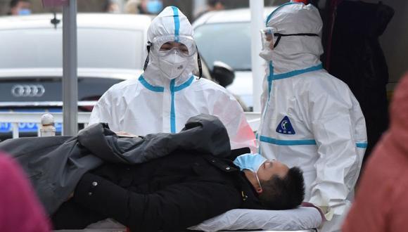 Trabajadores médicos que usan trajes protectores como precaución contra el coronavirus COVID-19 llevan a un paciente a la clínica de fiebre en un hospital en Beijing. (Foto: AFP / GREG BAKER).