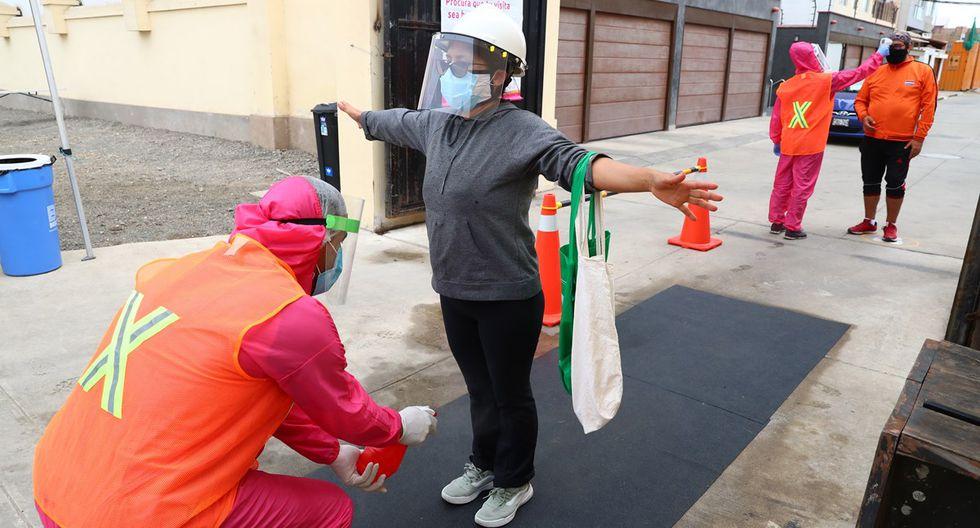 La casera ingresa por el pediluvio para limpiar zapatos y allí mismo rociarán un preparado de agua con alcohol a sus objetos de compra. (Foto: Alessandro Currarino)