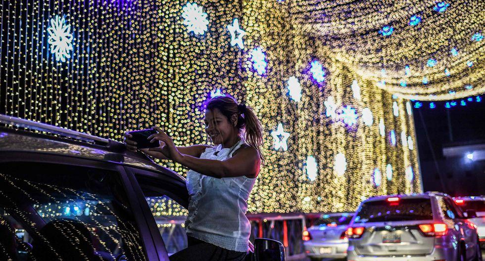 Una mujer sale por la ventana del auto para tomarse un selfie con las luces de Navidad colocadas en el puente sobre el río Guaire en Caracas, Venezuela. (AFP / Yuri CORTEZ).