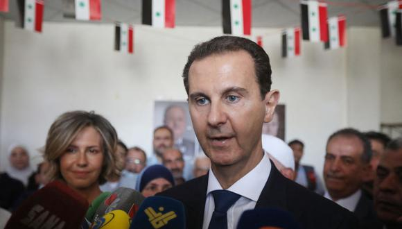 El presidente de Siria, Bashar al Asad, habla con los medios de comunicación después de emitir su voto con su esposa, Asma, en un colegio electoral en Douma, cerca de Damasco. (Foto de Louai Beshara / AFP).