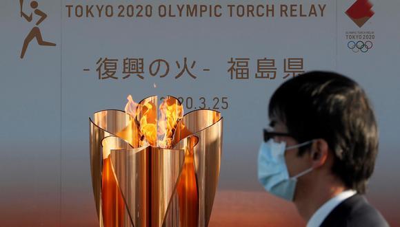 Un hombre con mascarilla pasa junto a la antorcha olímpica. EFE