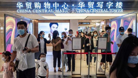 Las personas muestran sus códigos de salud en sus teléfonos inteligentes en la entrada de un centro comercial en Beijing. (Foto: AFP / NICOLAS ASFOURI).