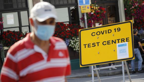 Un hombre con una máscara facial como precaución contra la transmisión del nuevo coronavirus pasa junto a un letrero que indica el camino hacia un centro de pruebas de COVID-19, en el norte de Londres, el pasado 16 de septiembre de 2020. (Tolga AKMEN / AFP)
