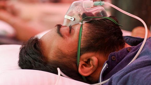 Un paciente de coronavirus Covid-19 respira con la ayuda de oxígeno proporcionado por un Gurdwara, un lugar de culto para los sijs, en Ghaziabad, India, el 6 de mayo de 2021. (Prakash SINGH / AFP).