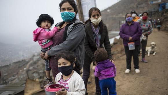 Un grupo de mujeres y sus hijos hacen fila para recibir comida gratis en el distrito de Villa María del Triunfo en Lima, Perú, en medio de la pandemia de coronavirus COVID-19. La imagen es del 17 de junio del 2020. (Foto: AP / Rodrigo Abd)
