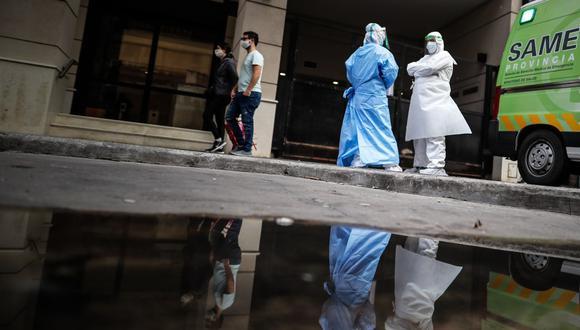 Imagen referencial. Una pareja pasa frente a personal médico con trajes de bioseguridad en Buenos Aires (Argentina). (EFE/Juan Ignacio Roncoroni).