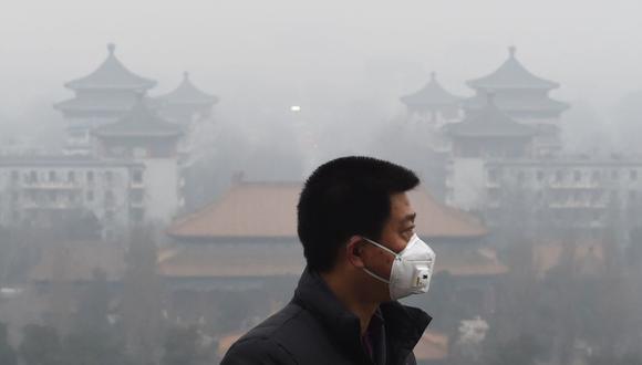 Un hombre usa una mascarilla para protegerse de la contaminación del aire en Beijing, China, el 8 de diciembre de 2015. (Foto de GREG BAKER / AFP).