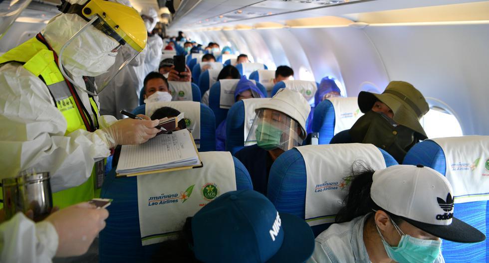 Personal sanitario chino inspecciona los documentos de los pasajeros a bordo de un avión proveniente de Vientiane, capital de Laos, que aterrizó en el aeropuerto internacional de Kunming Changshui, en Yunnan. El Comercio ha tomado conocimiento de 3 compatriotas varados en Laos y de otros 91 casos similares en el Sudeste Asiático. (Foto: CNS Photo via Reuters)