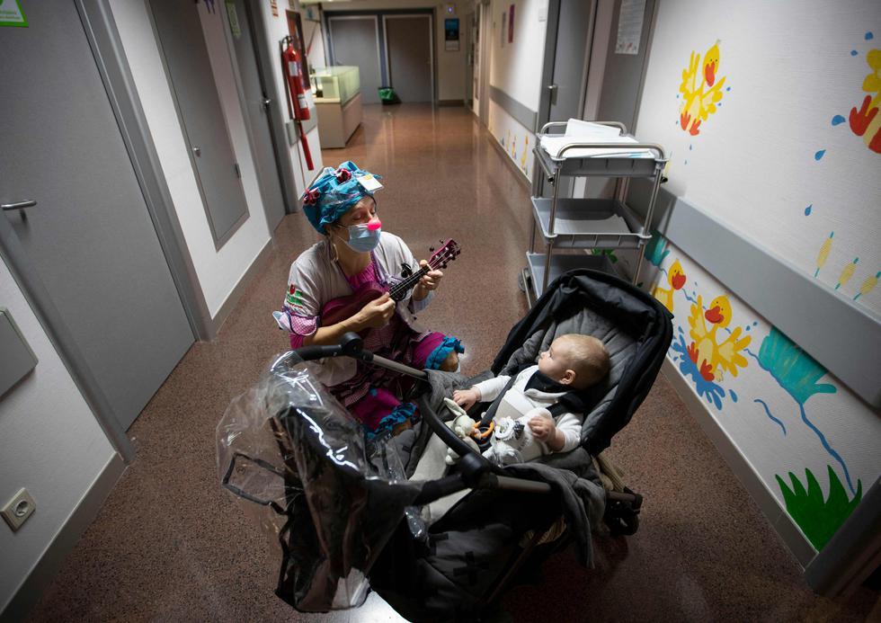 Una payasa de la ONG Sunrise Media (Medical Smile) actúa para Mario, un paciente de cinco meses, en el ala infantil del Hospital Son Llatzer de Palma de Mallorca, España. (Foto: Jaime Reina / AFP)