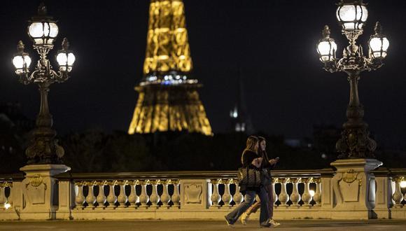 Dos peatones caminan por el puente Alexandre III poco antes del toque de queda nocturno por coronavirus en París (Francia), el 23 de octubre de 2020. (EFE/EPA/IAN LANGSDON).