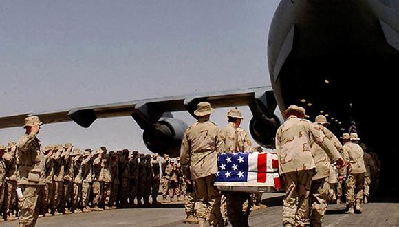 En esta foto de archivo tomada el 30 de marzo de 2003, los soldados estadounidenses llevan los ataúdes de sus colegas envueltos en banderas nacionales a un avión C-17 durante una ceremonia conmemorativa celebrada en la base del ejército de Kandahar, Afganistán. (Foto de SPC JOHN SLOSSER / POOL / AFP).