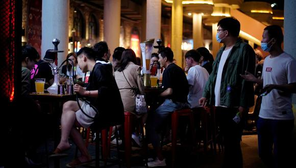 Imagen referencial. Las personas usan mascarillas en el área de un bar después de que reabrió después de un cierre debido al brote de la enfermedad del coronavirus (COVID-19), en Shanghai, China, 22 de mayo de 2020. (REUTERS/Aly Song).