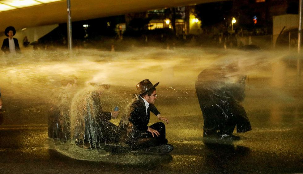 Israeli ultra-Orthodox Jewish men sit as a water canon is activated during a protest against the detention of a member of their community who refuses to serve in the Israeli army, in Jerusalem March 8, 2018. REUTERS/Ronen Zvulun     TPX IMAGES OF THE DAY