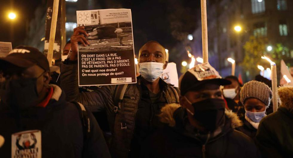 """Un manifestante sostiene un papel que dice """"Dormimos en la calle, esto hace frío, no tenemos zapatos, ni dinero, ni padres, ni escuela. ¿Cuáles son nuestros derechos? ¿Quién nos protege?"""", Mientras participa en una manifestación por la regularización de los inmigrantes indocumentados con motivo del Día Internacional del Migrante en París. (Foto: AFP / THOMAS COEX)."""