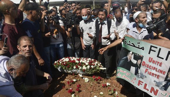 Los argelinos colocan rosas en la tumba del expresidente Abdelaziz Bouteflika durante su funeral en el cementerio El-Alia en la capital Argel el 19 de septiembre de 2021. (Foto: Ryad KRAMDI / AFP)