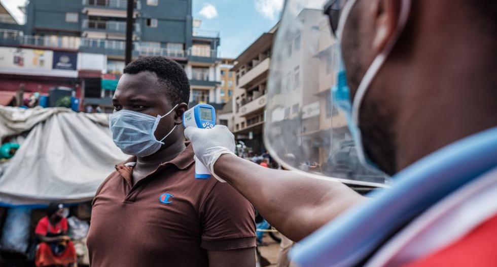 Un voluntario de la Cruz Roja mide la temperatura de un hombre antes de que se le permita ingresar al mercado de Nakasero en Kampala, Uganda, en medio de los esfuerzos por contener el coronavirus Covid-19. (Foto: Sumy Sadurni / AFP)