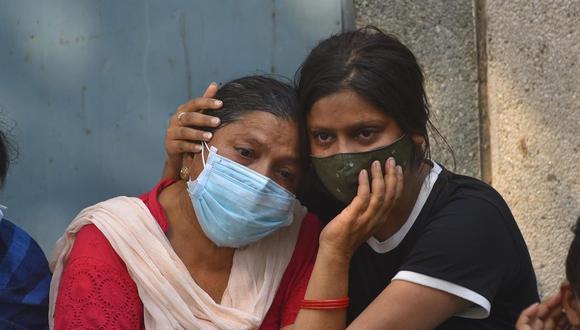 Familiares en duelo de una víctima de coronavirus COVID-19 en un campo de cremación en Nueva Delhi, India, el 29 de abril de 2021. (EFE / EPA / IDREES MOHAMMED).