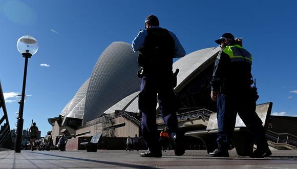Esta imagen tomada el 26 de junio de 2021 muestra a la policía de Australia patrullando frente a la Ópera de Sídney durante el cierre para frenar los contagios de cooronavirus. (SAEED KHAN / AFP).