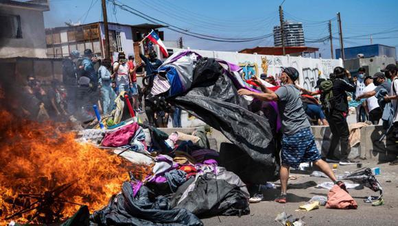 Manifestantes queman un campamento improvisado de migrantes venezolanos durante una marcha de protesta contra los inmigrantes en Iquique, Chile. (Foto: MARTIN BERNETTI / AFP).